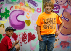 Two young kids, one with a spray can, at RedCan Jam 2019